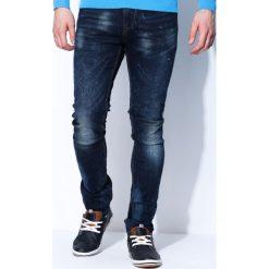 Granatowe Jeansy Alien. Czarne jeansy męskie z dziurami marki Born2be, l, z aplikacjami, z dresówki. Za 89,99 zł.