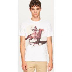 T-shirt z kowbojskim nadrukiem - Biały. Białe t-shirty męskie z nadrukiem marki Reserved, l. W wyprzedaży za 19,99 zł.