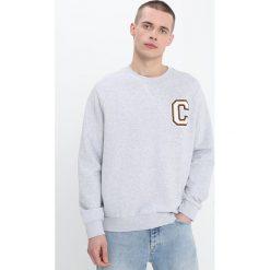 Calvin Klein KAMUS BADGE Bluza grey. Pomarańczowe kardigany męskie marki Calvin Klein, l, z bawełny, z okrągłym kołnierzem. W wyprzedaży za 411,75 zł.