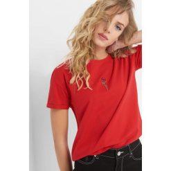 T-shirt z kwiatowym haftem. Czarne t-shirty damskie marki Orsay, xs, z bawełny, z dekoltem na plecach. Za 29,99 zł.