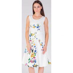 Rozkloszowana wizytowa sukienka ecru QUIOSQUE. Białe sukienki balowe marki QUIOSQUE, w kolorowe wzory, ze skóry ekologicznej, z krótkim rękawem, mini, rozkloszowane. W wyprzedaży za 79,99 zł.