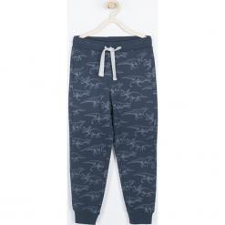 Spodnie. Niebieskie chinosy chłopięce DINOSAUR, z nadrukiem, z bawełny. Za 49,90 zł.
