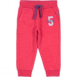 Spodnie. Czerwone chinosy chłopięce REBELS, z nadrukiem, z bawełny. Za 29,90 zł.