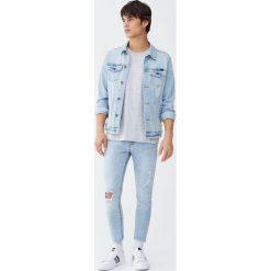 Krótkie jeansy super skinny fit z przetarciami. Czarne rurki męskie marki Pull&Bear, m. Za 129,00 zł.