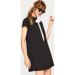 Sukienka z wiązaniem przy szyi - Czarny. Czarne sukienki z falbanami marki Reserved, l, z dekoltem na plecach. Za 79,99 zł.