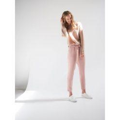Pastelowe spodnie chino - Różowy. Czarne chinosy damskie marki KIPSTA, z poliesteru, do piłki nożnej. Za 69,99 zł.