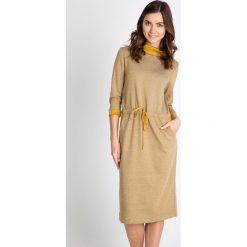 Beżowa sukienka z wiązaniem w pasie QUIOSQUE. Brązowe sukienki dzianinowe marki QUIOSQUE, na jesień, z golfem. W wyprzedaży za 99,99 zł.