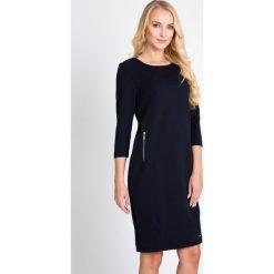 Prążkowana sukienka z zamkami na biodrach QUIOSQUE. Szare sukienki balowe marki QUIOSQUE, do pracy, z dzianiny, z klasycznym kołnierzykiem, z długim rękawem, proste. W wyprzedaży za 99,99 zł.