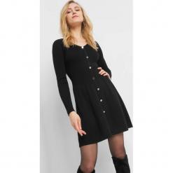 Dzianinowa sukienka z guzikami. Czarne sukienki dzianinowe marki Orsay, xs, dekolt w kształcie v, plisowane. Za 119,99 zł.