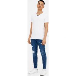 Ciemnoniebieskie jeansy skinny fit z przetarciami. Szare jeansy męskie relaxed fit marki Pull & Bear, okrągłe. Za 69,90 zł.