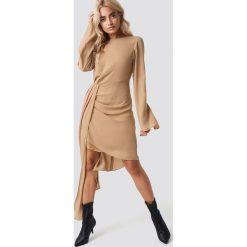 NA-KD Party Sukienka z drapowanym detalem - Beige. Brązowe sukienki asymetryczne marki NA-KD Party, na imprezę, z tkaniny, z asymetrycznym kołnierzem, midi. Za 202,95 zł.