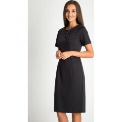 Czarna sukienka z koralikami przy dekolcie QUIOSQUE. Czarne długie sukienki marki QUIOSQUE, na imprezę, na lato, z dzianiny, z długim rękawem. W wyprzedaży za 159,99 zł.