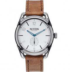 """Zegarek kwarcowy """"C39"""" w kolorze brązowo-srebrno-białym. Brązowe, analogowe zegarki męskie Nixon, ze stali. W wyprzedaży za 454,95 zł."""