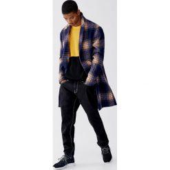 Dzianinowy sweter z fakturą i kolorowymi panelami. Żółte swetry klasyczne męskie Pull&Bear, m, w kolorowe wzory, z dzianiny. Za 99,90 zł.