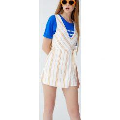 Kombinezon ze spódnicospodniami i kopertowym dekoltem. Szare kombinezony damskie Pull&Bear, z kopertowym dekoltem. Za 69,90 zł.