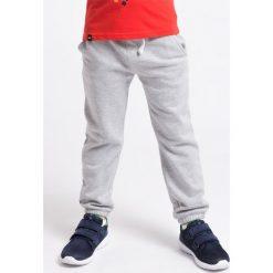 Spodnie chłopięce: Spodnie dresowe dla małych chłopców JSPMD101 – jasny szary melanż – 4F