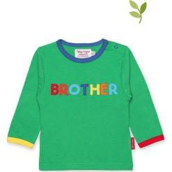 Koszulka w kolorze zielonym. Zielone bluzki dziewczęce bawełniane Toby Tiger, z aplikacjami, z okrągłym kołnierzem, z długim rękawem. W wyprzedaży za 85,95 zł.