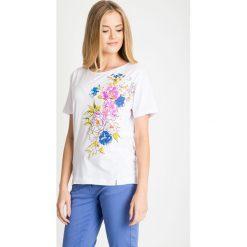 Biała bawełniana bluzka z kwiatami QUIOSQUE. Białe bluzki z odkrytymi ramionami QUIOSQUE, z nadrukiem, z bawełny, biznesowe, z okrągłym kołnierzem, z krótkim rękawem. W wyprzedaży za 29,99 zł.