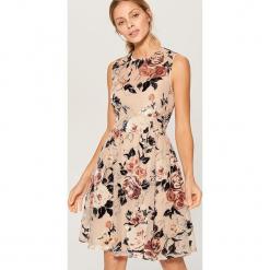 Rozkloszowana sukienka w kwiaty - Wielobarwn. Różowe sukienki rozkloszowane marki Mohito, w kwiaty. Za 169,99 zł.