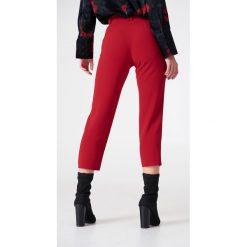 NA-KD Trend Spodnie z surowo wykończonymi nogawkami - Red. Białe spodnie z wysokim stanem marki NA-KD Trend, z nadrukiem, z jersey, z okrągłym kołnierzem. Za 161,95 zł.