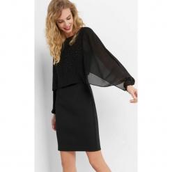 Sukienka z pelerynką. Czarne sukienki dzianinowe marki Orsay, s, wizytowe, z dekoltem na plecach, dopasowane. Za 159,99 zł.