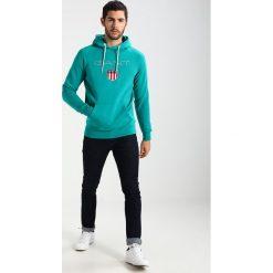 GANT SHIELD HOODIE Bluza z kapturem emerald green. Zielone kardigany męskie GANT, m, z bawełny, z kapturem. W wyprzedaży za 377,10 zł.