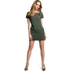 COCO Sukienka mini z naszywką - militarno zielona. Zielone sukienki dresowe Moe, s, z aplikacjami, mini, dopasowane. Za 109,00 zł.