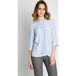 Błękitna elegancka bluzka z falbaną na przodzie BIALCON. Białe bluzki na imprezę marki Born2be, s, w kwiaty, z koronki, z dekoltem na plecach, z długim rękawem. W wyprzedaży za 178,00 zł.