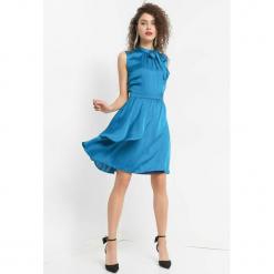Asymetryczna sukienka z kokardą. Czarne sukienki asymetryczne marki KIPSTA, m, z elastanu, z długim rękawem, na fitness i siłownię. Za 159,99 zł.