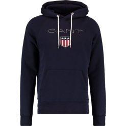 GANT SHIELD HOODIE Bluza z kapturem evening blue. Niebieskie bluzy męskie rozpinane marki GANT, m, z bawełny, z kapturem. W wyprzedaży za 347,65 zł.