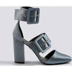 NA-KD Shoes Czółenka na słupku z klamrami - Grey. Szare buty ślubne damskie marki NA-KD Shoes, w paski, na wysokim obcasie, na obcasie. W wyprzedaży za 113,37 zł.