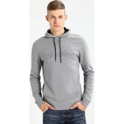 Calvin Klein KAMS FRENCH TERRY HOOD LOGO Bluza grey. Pomarańczowe kardigany męskie marki Calvin Klein, l, z bawełny, z okrągłym kołnierzem. W wyprzedaży za 384,30 zł.
