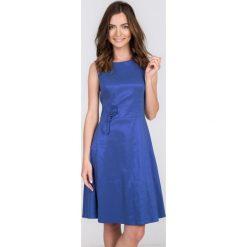 Granatowa rozkloszowana sukienka z kokardką QUIOSQUE. Niebieskie sukienki mini marki QUIOSQUE, na imprezę, z satyny, eleganckie, z kokardą, bez rękawów, dopasowane. W wyprzedaży za 59,99 zł.