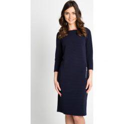 Granatowa prążkowana sukienka QUIOSQUE. Szare sukienki dzianinowe marki QUIOSQUE, do pracy, w prążki, biznesowe, z dekoltem na plecach, z długim rękawem. W wyprzedaży za 79,99 zł.
