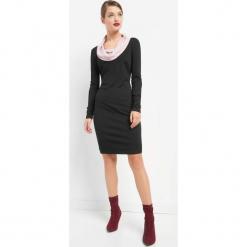 Dopasowana sukienka. Czarne sukienki dzianinowe marki Orsay, do pracy, biznesowe, z golfem, dopasowane. W wyprzedaży za 95,00 zł.