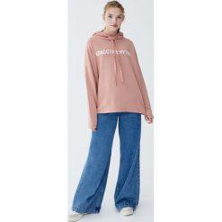 Bluza z kapturem i napisem po rosyjsku. Czerwone bluzy z kapturem damskie Pull&Bear, z napisami. Za 59,90 zł.