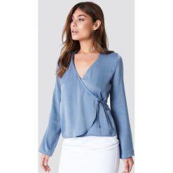 NA-KD Satynowa koszula z kopertowym przodem - Blue. Niebieskie koszule wiązane damskie marki NA-KD, z poliesteru, z kopertowym dekoltem. Za 80,95 zł.