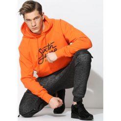 Pomarańczowa Bluza Enclosure. Czarne bluzy męskie rozpinane marki Born2be, m, z nadrukiem, z dresówki, z kapturem. Za 129,99 zł.