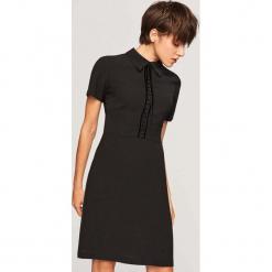 Sukienka z kołnierzem - Czarny. Białe sukienki z falbanami marki Reserved, l, z dzianiny. Za 99,99 zł.