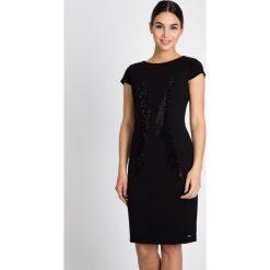 Czarna sukienka z błyszczącym wzorem QUIOSQUE. Czarne sukienki QUIOSQUE, na imprezę, z tkaniny, eleganckie, z kopertowym dekoltem, mini, dopasowane. W wyprzedaży za 149,99 zł.