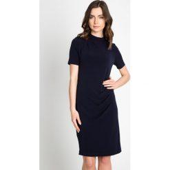 Granatowa sukienka z marszczeniem QUIOSQUE. Szare sukienki mini marki QUIOSQUE, ze stójką, z krótkim rękawem. W wyprzedaży za 99,99 zł.