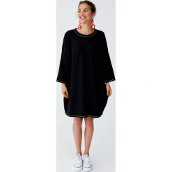 Sukienka kokon z kontrastowymi szwami. Czarne sukienki z falbanami marki Pull&Bear, z kontrastowym kołnierzykiem. Za 62,90 zł.
