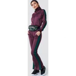 NA-KD Spodnie sportowe z rozcięciem - Purple. Fioletowe bryczesy damskie NA-KD, z poliesteru. Za 161,95 zł.