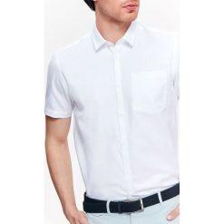 KOSZULA MĘSKA ZE STRUKTURALNEJ TKANINY O KROJU REGULAR. Brązowe koszule męskie na spinki marki QUECHUA, m, z elastanu, z krótkim rękawem. Za 49,99 zł.