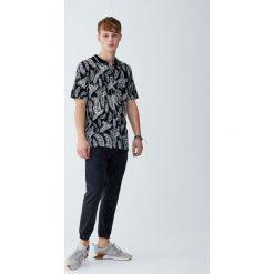 Koszulka polo z tropikalnym nadrukiem liści. Czarne koszulki polo Pull&Bear, m, z nadrukiem, z krótkim rękawem. Za 59,90 zł.