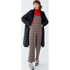 Pikowany płaszcz z podszewką ze sztucznego futerka. Czarne płaszcze damskie marki Pull&Bear. Za 299,00 zł.