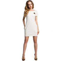 Ecru Dopasowana Mini Sukienka z Ozdobną Naszywką. Białe sukienki dzianinowe marki bonprix, na plażę, w koronkowe wzory. Za 88,90 zł.