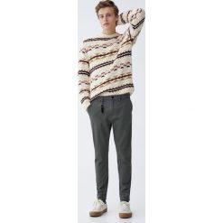 Spodnie chinosy carrot. Brązowe chinosy męskie Pull&Bear. Za 89,90 zł.