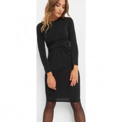 Sukienka z marszczeniem w talii. Czarne sukienki dzianinowe Orsay, z aplikacjami, wizytowe, z dekoltem na plecach, dopasowane. Za 119,99 zł.
