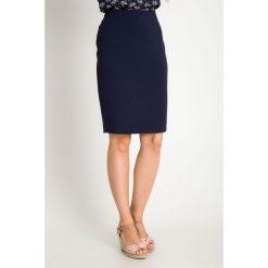 Klasyczna ołówkowa granatowa spódnica QUIOSQUE. Czarne spódnice wieczorowe marki QUIOSQUE, na imprezę, z dzianiny, z kopertowym dekoltem, mini, dopasowane. W wyprzedaży za 99,99 zł.